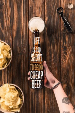 cropped image of woman pouring beer into glass at wooden table with crispy chips, with