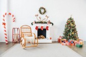 decorated room with rocking chair, christmas tree and presents for winter holidays celebration