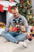 Fotografia uomo sorridente con la tazza di bevanda calda e cane chihuahua vicino da in sala per la celebrazione di Natale