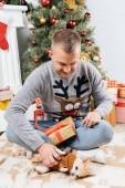mladý muž s vánoční prezentovat, hrát si s chihuahua pejsek doma