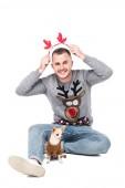 glücklicher Mann mit festlichen Hirschhörnern auf dem Kopf und kleinem Chihuahua-Hund in der Nähe isoliert auf weißem Grund