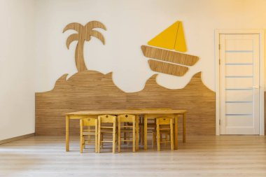 cozy room with wooden table and chairs and decorative elements in wall in modern kindergarten