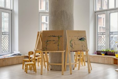 easels and wooden chairs in classroom at modern kindergarten
