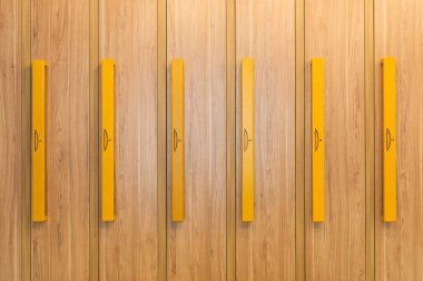 full frame view of wooden lockers with yellow handles in kindergarten