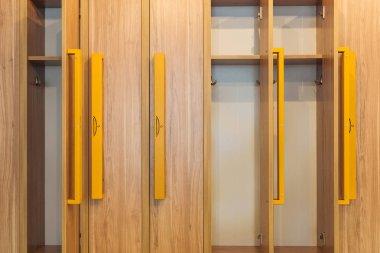 full frame view of wooden lockers with yellow handles in kindergarten cloakroom