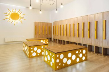 wooden lockers in modern illuminated kindergarten cloakroom