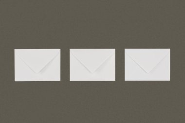 Top view of three closed white envelopes arranged isolated on grey background stock vector