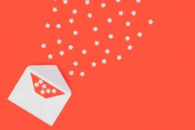 top view of open white envelope with red card and small white stars isolated on red background