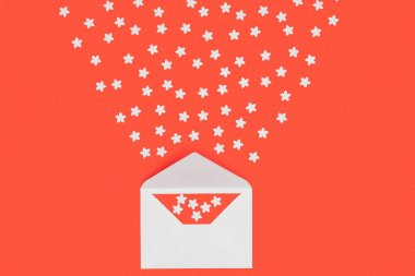 close-up view of white envelope with red card and small white stars isolated on red
