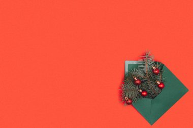 green envelope with fir twigs and shiny christmas baubles isolated on red