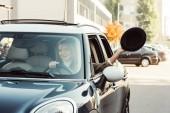 Fotografie Selektivní fokus veselá žena vyklání ruku s černým kloboukem, zatímco sedí v autě na městské ulici