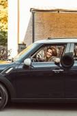 Fotografie usmívající se žena vyklání ruku s černým kloboukem, zatímco sedí v autě na městské ulici