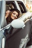 Fotografia donna adulta felice in cappello nero esamina ala specchio mentre facendo il make up in auto