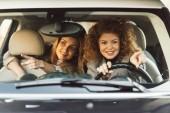 Fotografie šťastné ženy přátelé směřující prsty k sobě zatímco sedí v autě