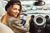 Erwachsene, fröhliche Frau mit schwarzem Hut und karierter Jacke sitzt am Steuer im Auto
