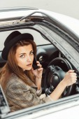 Fotografia Ritratto della donna alla moda in cappello nero ne su smartphone mentre era seduto al volante in auto