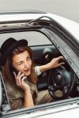 Fotografia donna felice in cappello nero sbattere le palpebre e ne su smartphone mentre era seduto al volante in auto