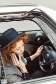 Fotografia vista di alto angolo della donna di redhead in cappello nero ne su smartphone mentre era seduto al volante in auto