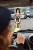 Fotografia immagine potata della donna che si siede al volante mentre elegante turista femminile in piedi con trolley presso city street