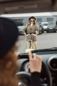 Fotografia immagine potata della donna che si siede al volante mentre elegante turista femminile che sta con le mani sulla vita vicino a trolley presso via della città