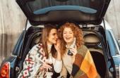 boční pohled na usmívající se žena s soda láhev šeptal smát zrzka žena přítel v kufru auta na ulici
