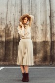 Fotografie stylish curly redhead woman in beige turtle neck and skirt posing at city street