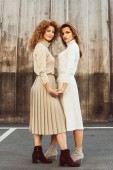 Photo beautiful female models in turtle necks and skirts holding hands at urban street