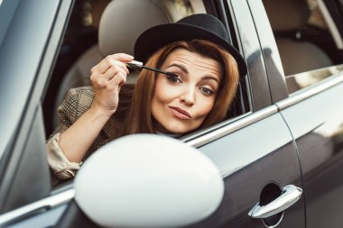 Beautiful woman in black hat looking at side mirror while using ink for eyelashes in car stock vector