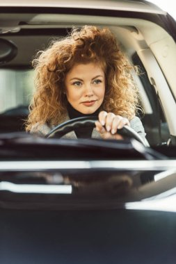 Portrait of beautiful cheerful ginger curly woman driving car stock vector