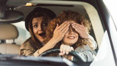 Selective focus of shocked woman covering eyes to female friend while she driving car stock vector