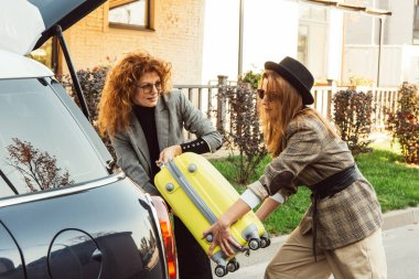attractive redhead woman helping putting wheeled bag in car trunk for female tourist in car trunk