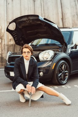 fashionable adult woman in coat and eyeglasses posing with spanner near car with opened hood at urban street