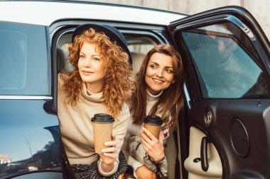 happy stylish female friends with disposable coffee cups looking out from car at street
