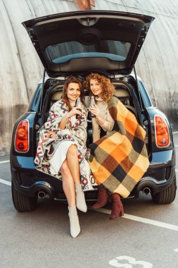 cheerful female friends wrapped in blankets holding soda bottles sitting in car trunk at urban street