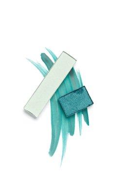 flat lay with arranged eyeshadows of blue shades on white background