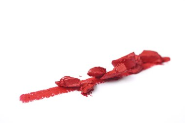 close up view of smashed red lipstick on white background