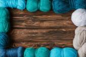 Fotografie flache Lay mit angeordneten blauen, weißen und grünen Garn Clews auf hölzernen Tischplatte