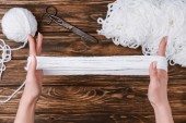 Fotografie partial view of woman holding white yarn for knitting on hands on wooden tabletop with scissors