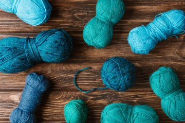 top view of green and blue knitting yarn clews on wooden surface