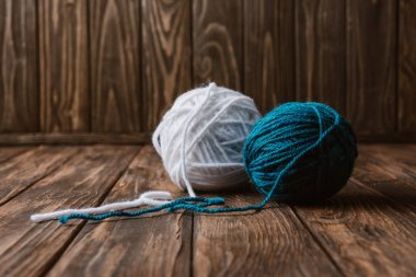 close up view of white and blue yarn balls on wooden tabletop