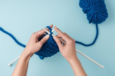 cropped shot of woman knitting on blue background with blue yarn