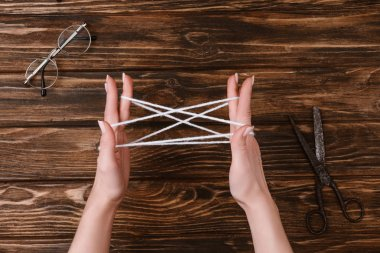 partial view of woman holding white yarn for knitting on hands on wooden tabletop with eyeglasses and scissors