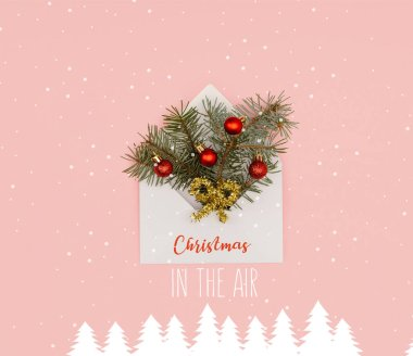 Top view of white envelope with fir twigs and shiny christmas baubles isolated on pink with