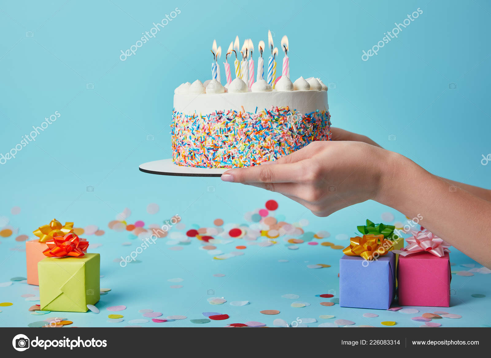 Cropped View Of Woman Holding Birthday Cake With Candles On Blue Background Confetti And Gifts Stock Image