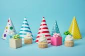 bunte Party-Hüte, Geschenke und leckere Cupcakes auf blauem Hintergrund