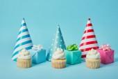 Színes fél sapkák, ajándékok és ízletes cupcakes a kék háttér