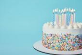 Lahodné narozeninový dort se svíčkami osvětlení na modrém pozadí