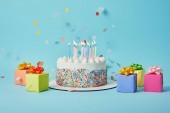 Chutný dort se svíčkami, barevné dárky a konfety na modrém pozadí