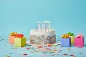 Fotografie Lahodný dort se svíčkami, barevné dárky a konfety na modrém pozadí