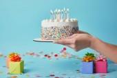Vágott nézet nő gazdaság születésnapi torta gyertyákkal, a kék háttér konfetti és ajándékok